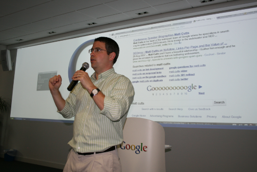 MAtt Cutts taliking about SEO in green shirt with white stripes....